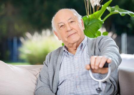 personas mirando: Retrato del hombre mayor Holding metal Ca�a Foto de archivo