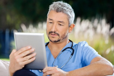 Male Caretaker Using Tablet PC While Sitting photo
