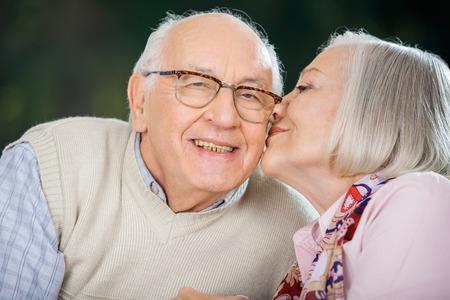 Senior donna baciare On Mans Cheek Archivio Fotografico