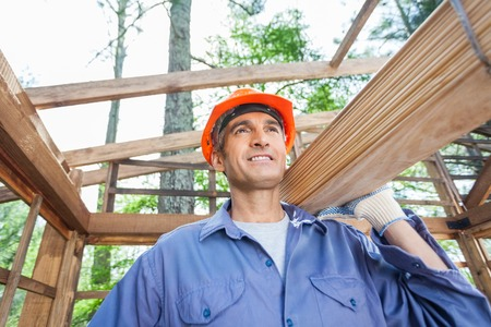 Construction Worker Carrying Wooden Planks