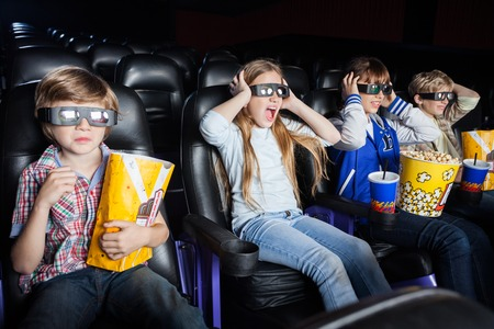 3d: Scared Children Watching 3D Movie In Cinema Theater Stock Photo