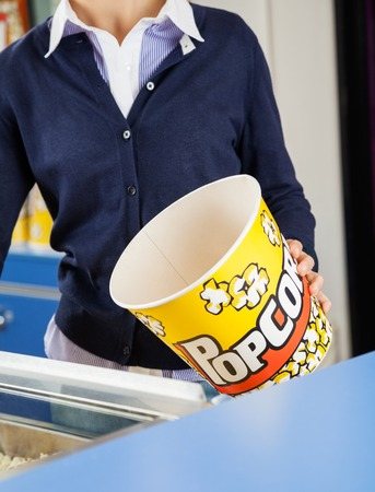 Happy Worker Offering Popcorn At Cinema Concession Stand Stock Photo ...