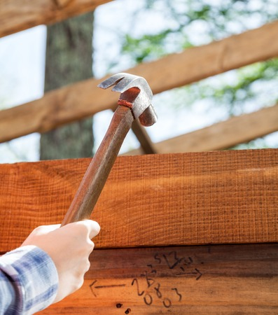 timber frame: Workers Hand Hammering Nail On Timber Frame At Site Stock Photo