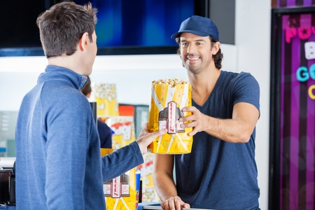 selling service smile: Worker Selling Popcorn To Man At Concession Stand Stock Photo