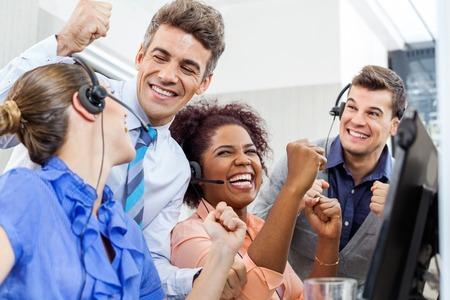 Cheerful Customer Service Representatives And Manager Celebratin