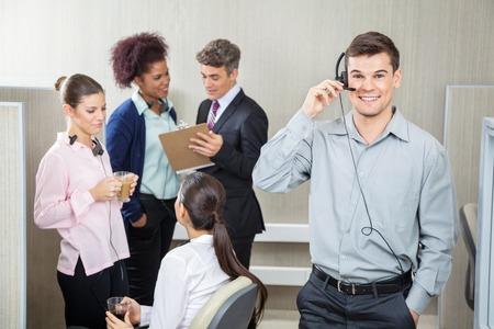 callcenter: Happy Male Customer Service Representative Using Headphones Stock Photo