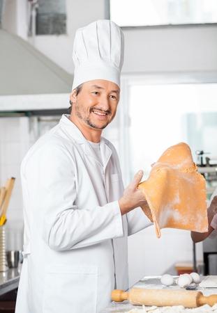 toque blanche: Happy Chef Holding Ravioli Pasta Sheet In Kitchen Stock Photo