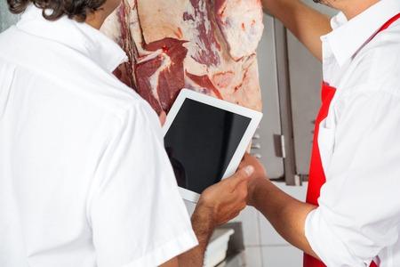 prime adult: Butchers Holding Digital Tablet In Meat Shop