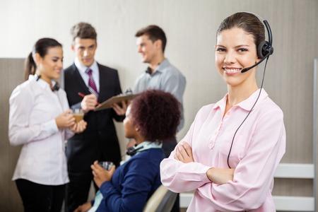 customer service representative: Confident Customer Service Representative Standing Arms Crossed Stock Photo