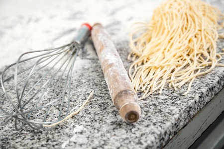 wire pin: Spaghetti Pasta With Rolling Pin And Wire Whisk On Countertop Stock Photo