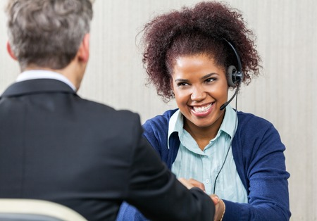 Happy Female Customer Service Agent Shaking Hands With Manager photo