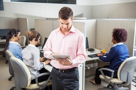 콜 센터에서 태블릿 컴퓨터를 사용하는 사업가 스톡 콘텐츠