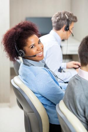 customer service phone: Smiling Female Customer Service Representative In Office Stock Photo