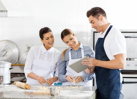 cocinero: Felices Chefs Comprobaci�n de receta En Tableta digital en cocina