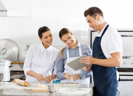 food industry: Happy Chefs Checking Recipe On Digital Tablet In Kitchen
