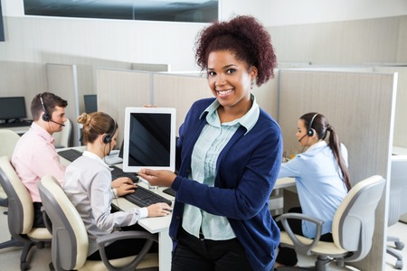 comp: Confident Customer Service Representative Displaying Tablet Comp