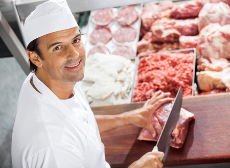 butcher shop: Confident Butcher Cutting Meat At Counter Stock Photo