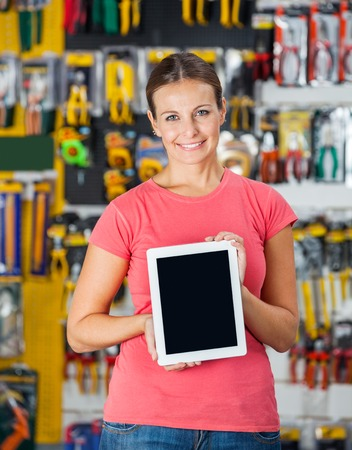 Woman Showing Digital Tablet In Hardware Shop photo