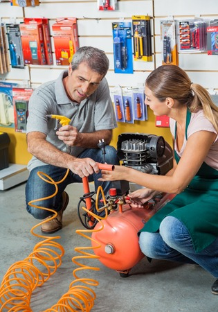 compressed air hose: Saleswoman Showing Air Compressor To Customer In Store Stock Photo