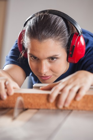 Concentrated Carpenter Cutting Wood With Tablesaw photo