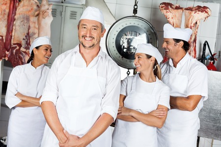 Male Butcher With Team In Butchery photo