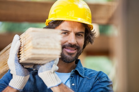 laborers: Smiling Worker Carrying Tied Wooden Planks Stock Photo