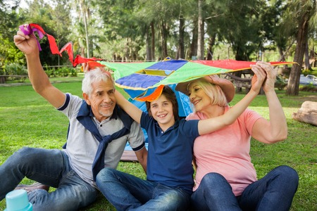 staycation: Happy Boy With Grandparents Holding Kite At Campsite Stock Photo
