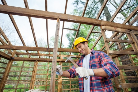 hammering: Smiling Worker Hammering Nail On Timber Cabin
