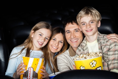 Happy Family With Popcorn At Cinema Theater Stock Photo