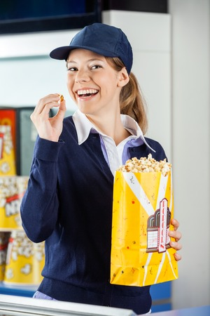 concession: Cheerful Worker Eating Popcorn At Cinema Concession Stand