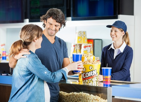 concession: Expectant Couple Buying Snacks At Concession Stand Stock Photo