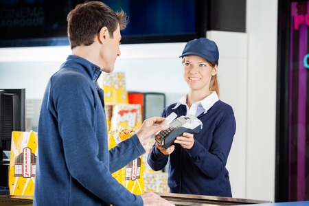Worker Accepting Payment From Man Through NFC Technology At Cine