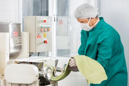 workwear: Chef In Protective Workwear Processing Spaghetti Pasta Sheet