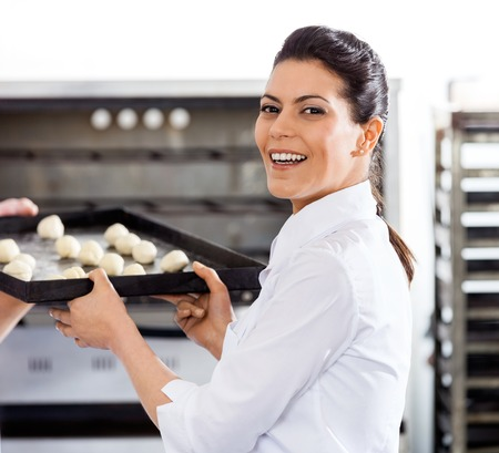 toque blanche: Happy Chef Giving Baking Sheet To Colleague By Oven Stock Photo