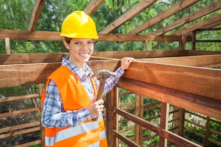 Confident Female Worker Holding Hammer In Timber Frame photo