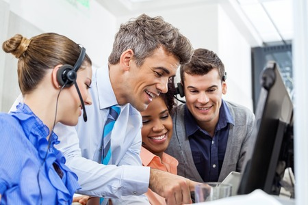 Manager With Team Using Tablet PC In Office photo