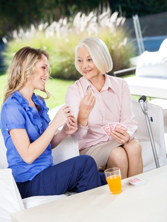 residents: Happy Grandmother Showing Playing Card To Granddaughter