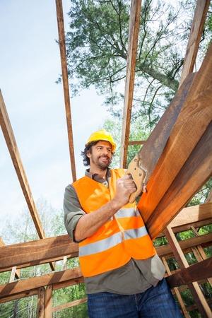 handsaw: Trabajador de cortar madera con serrucho En Construcci�n Sitio