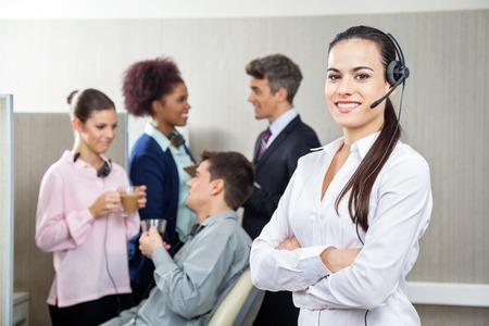 Smiling Female Customer Service Representative Standing Arms Cro photo