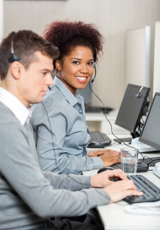 computer support: Young Employee With Male Colleague Working In Office