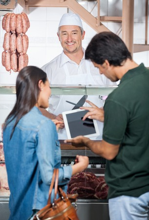 meat counter: Happy Butcher With Couple Using Digital Tablet