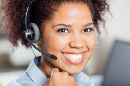 Glückliche weibliche Kundendienstmitarbeiter tragender Kopfhörer Standard-Bild