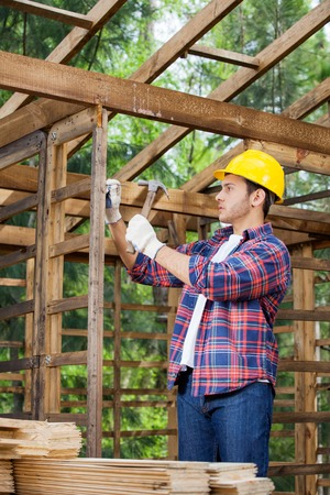 hammering: Construction Worker Hammering Nail On Wooden Cabin Stock Photo