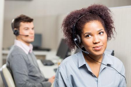 handsfree phone: Female Customer Service Representative Wearing Headset In Office Stock Photo