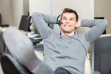 troubleshoot: Relaxed Smiling Customer Service Representative With Legs On Des Stock Photo