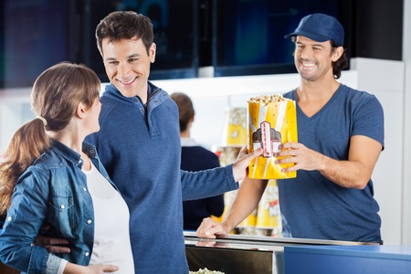 concession: Expectant Couple Buying Popcorn At Concession Stand