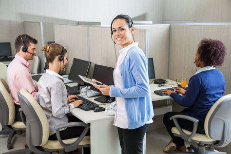 Customer Service Executive Standing By Colleagues Working At Des photo