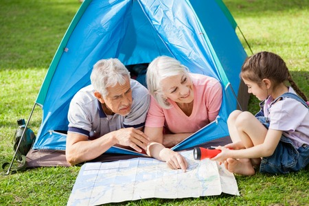 staycation: Grandparents With Granddaughter Discussing Over Map At Campsite