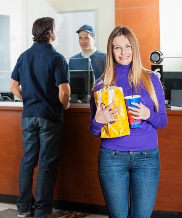 selling service smile: Beautiful Woman Holding Snacks While Man Buying Movie Tickets