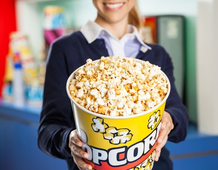 concession: Worker Offering Popcorn Bucket At Cinema Concession Stand